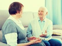 Elderly couple warmly talk. Elderly couple friendly talking sitting at home on sofa Stock Photos
