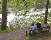 An Elderly Couple Watch Rowboats in a Lake Royalty Free Stock Image