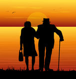 Elderly couple watching the sea. In the sunset Royalty Free Stock Photo