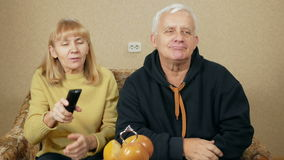 An elderly couple watching television at home on the couch. Woman laughing picks TV remote control itself and choose stock video footage
