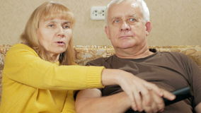 An elderly couple watching television at home on the couch. Woman laughing picks TV remote control itself and choose stock video