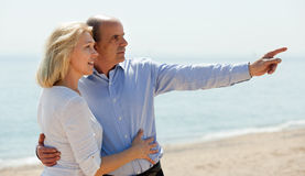 Elderly couple in years at seashore vacation pointing Stock Images