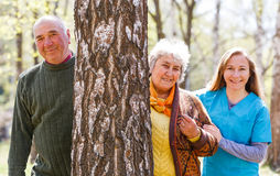 Elderly couple and young caregiver Stock Image