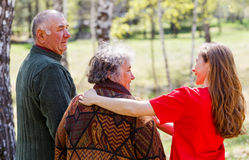 Elderly couple and young caregiver Stock Photos