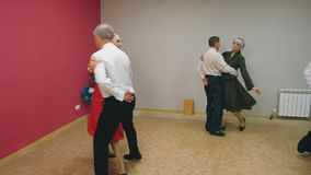 Elderly couples are dancing waltz in elegant clothes.