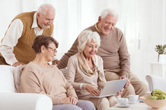 Elderly couples looking at laptop Stock Photo