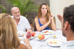 Elderly daughter with father listening to discussion. Happy family talking while having food on terrace Royalty Free Stock Photo