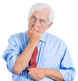 Elderly, desperate, mad, crazy looking man, biting his fist Royalty Free Stock Image