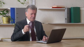 Elderly director use laptop at work. Middle aged businessman sitting at the working place in the office with wooden desk. Grey haired man using computer stock video