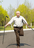 Elderly disabled man balancing on one leg Stock Images
