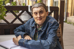 Elderly disabled man with cerebral palsy writing in notebook. Royalty Free Stock Photos