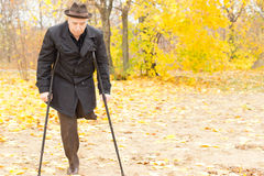 Elderly disabled man on crutches in a park stock image