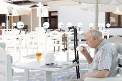 Elderly disabled man enjoying a cup of coffee Stock Images