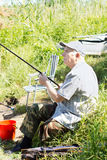 Elderly disabled man fishing on a river bank Royalty Free Stock Image