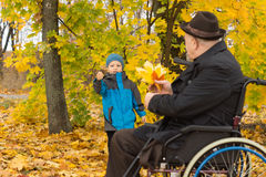 Elderly disabled man playing with his grandson Stock Photo