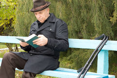 Elderly disabled man sitting outdoors reading Stock Photo