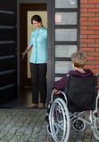 Elderly disabled woman enters the house. Elderly disabled women in a wheelchair enters the house royalty free stock photo