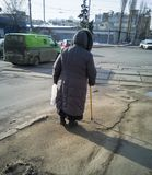 Elderly disabled woman with a stick walking down the street royalty free stock image