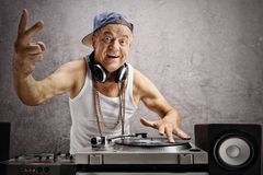 Elderly DJ making a peace sign. Against a rusty gray wall Stock Photography