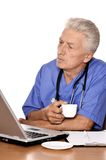 Elderly doc with a laptop Royalty Free Stock Images
