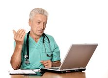 Elderly doc with a laptop Royalty Free Stock Photography