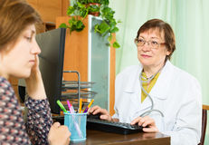 Elderly doctor advises female patient Royalty Free Stock Photography
