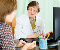 An elderly doctor advises a woman Stock Image