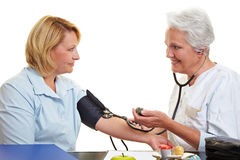 Elderly doctor with blood pressure Royalty Free Stock Photos