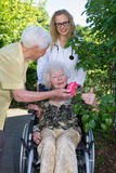 Elderly with Doctor and Caregiver at the Garden Stock Photos