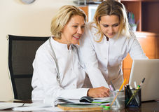 Elderly doctor consulting young female colleague Stock Photography