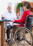 Elderly doctor and disabled women in wheelchair Stock Photography