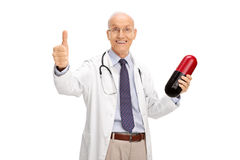 Elderly doctor holding a pill and giving a thumb up. Joyful elderly doctor holding a big pill and giving a thumb up isolated on white background Royalty Free Stock Photography