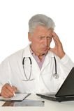 Elderly doctor with a laptop Royalty Free Stock Image