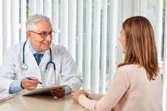 Elderly doctor man with patient woman. Royalty Free Stock Image