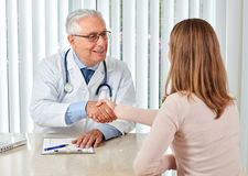 Elderly doctor man with patient woman. Royalty Free Stock Photos
