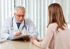 Elderly doctor man with patient woman. stock images