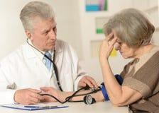 Elderly doctor measuring blood pressure Royalty Free Stock Image