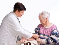 Elderly doctor and patient. Measuring pressure. Royalty Free Stock Photography