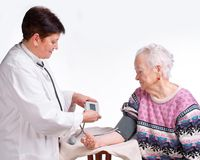 Elderly doctor and patient. Measuring pressure. Royalty Free Stock Image