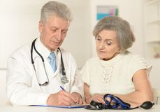Elderly doctor with patient Stock Image