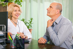 Elderly doctor talking with aged male patient Stock Photography