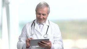Elderly doctor typing on pc tablet. Senior male doctor using computer tablet on blurred background. People, profession, technology stock video footage
