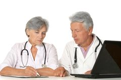 Elderly doctors with a laptop. Isolated on a white background Stock Photos
