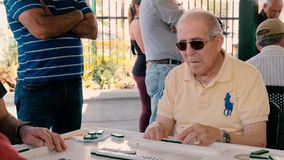 Elderly domino game players video. Miami, Florida USA - January 19, 2019: High definition slow motion video of elderly individuals playing the popular domino stock video footage