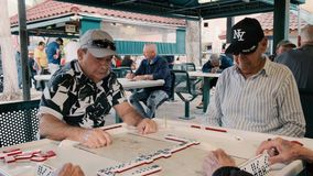 Elderly Domino Game Players Video. Miami, Florida USA - January 19, 2019: High definition video of elderly individuals playing the popular domino game at the stock video footage