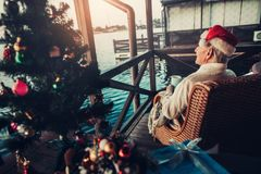 Elderly dreamy male person having some rest. Christmas in cottage on lake. Mature man sitting on armchair and looking at water. Small decorated tree on table stock photography