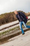 Elderly energetic man running along a beach Royalty Free Stock Images