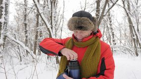 Elderly European man opens a thermos bottle and pours tea into a cup in the snow-covered forest. Thick dense thicket of. Elderly European man opens a thermos and stock footage