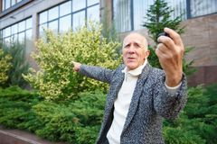 An elderly man, holding a action camera and showing his hand direction. Outdoors on the street. royalty free stock photos