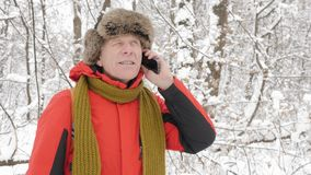 Elderly european smiling man talking on a smartphone in a snowy forest. Thick dense thicket of trees and roots in in the. Snow-covered forest. Hike and travel stock video footage